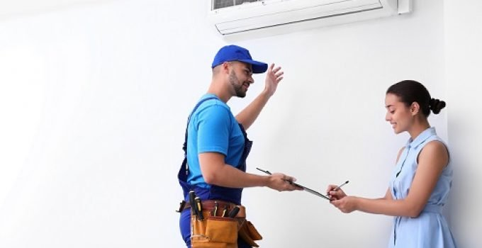 Technician speaking with woman about air conditioner